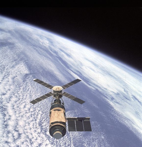 An overhead view of the Skylab Orbital Workshop in Earth orbit as photographed from the Skylab 4 Command and Service Modules (CSM) during the final fly-around by the CSM before returning home. The space station is contrasted against the pale blue Earth